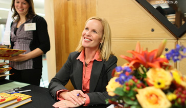 Media Relations Coach-PR Consultant-Elisabeth Leamy-Signs books at a Convention